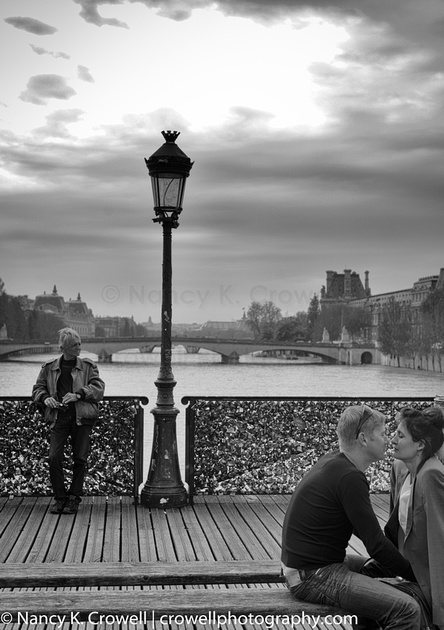 Two lovers on the Ponts des Arts bridge in Paris are oblivious to their surroundings.