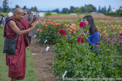 Image of monk in burgundy robes taking a photo of a woman standing next to dahlias with a phone camera.