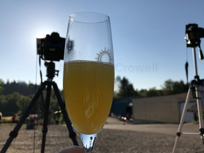 Image of Champagne glass full of champagne and orange juice, with camera on tripod in background.