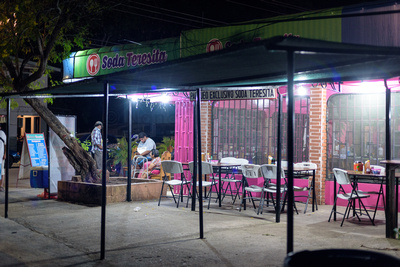 """Brightly lit tables and chairs outside a local """"Soda"""" restaurant."""