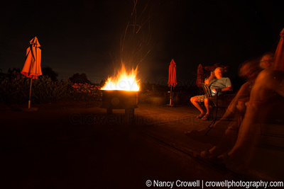 Image of fire in fire pit and people sitting around it.