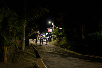 People walking down a dimly lit dirt road toward a lighted cabana.