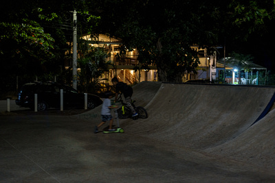 Two children playing at a skate park, one on a bicycle, one on a scooter.