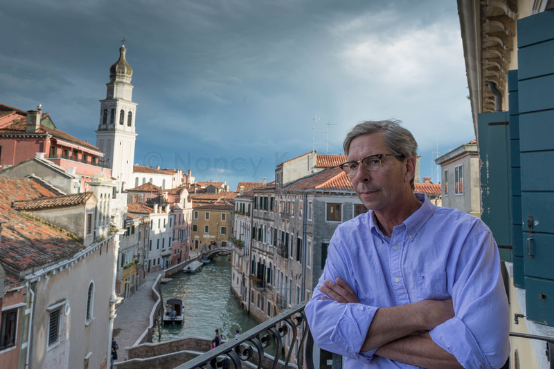 Image of my husband looking over a balcony in Venice with the city and canals in the background.